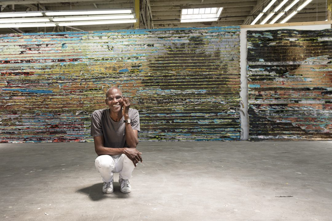 Mark Bradford, seen in his Los Angeles studio with a detail of Pickett's Charge, 2017. Mixed media. Courtesy of the artist and Hauser & Wirth. Photo: Agata Gravante