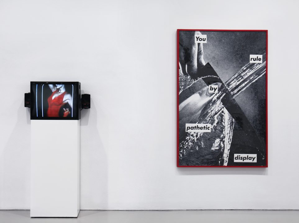 "Installation view of Brand New: Art and Commodity in the 1980s at the Hirshhorn Museum and Sculpture Garden, 2018. Left to right: Martha Rosler, Martha Rosler Reads ""Vogue"", 1982; Barbara Kruger, Untitled (You Rule by Pathetic Display), 1982. Photo: Cathy Carver."