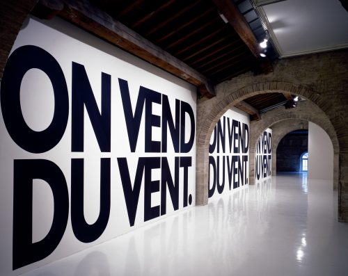 Haim Steinbach, on vend du vent, 1988. Text in matte black latex paint, or vinyl letters applied onto the wall; dimensions variable. Courtesy the artist and Tanya Bonakdar Gallery, New York