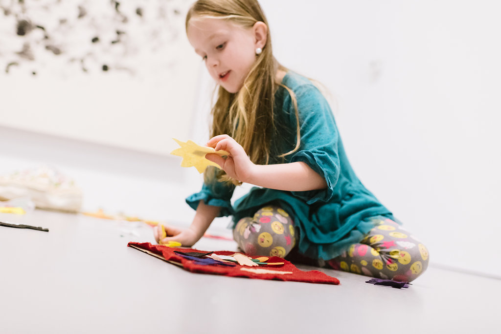 Child playing with LEGOs in gallery