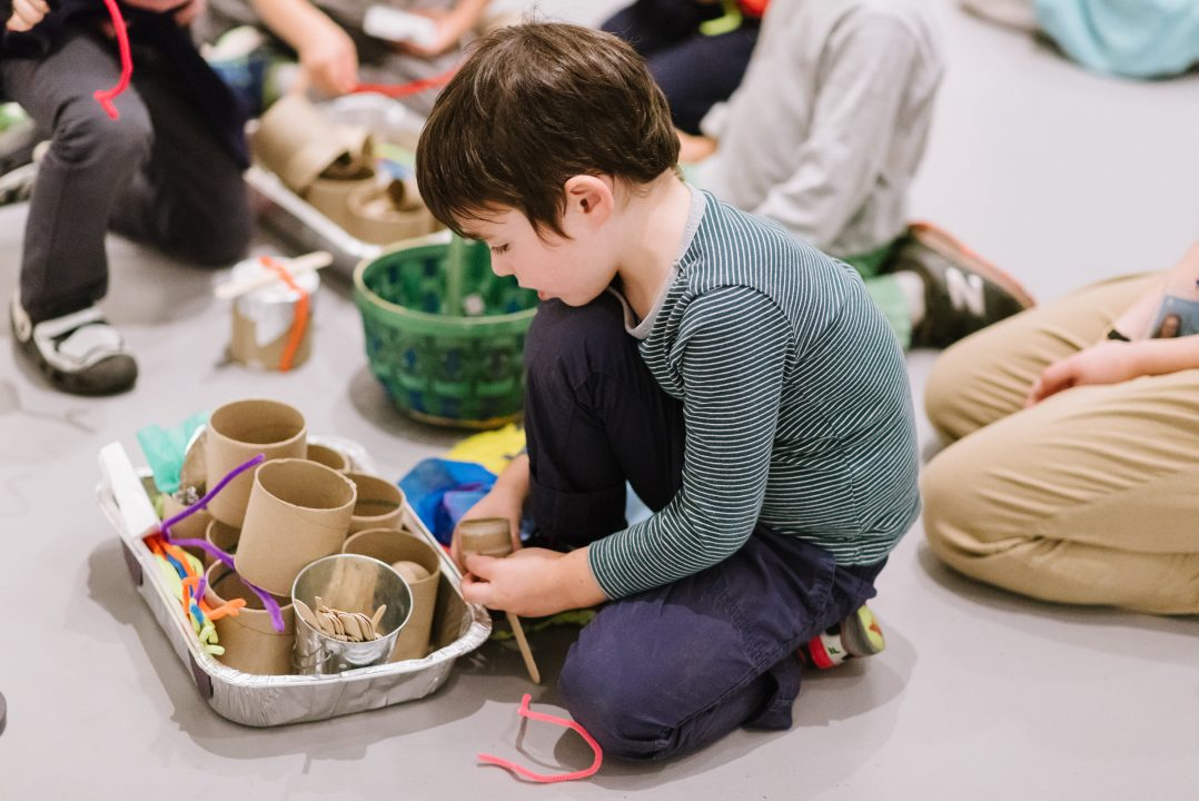Child playing with yarn, participating in activity in gallery.