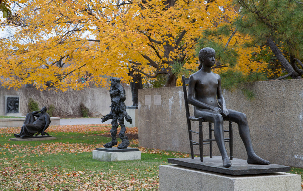 Hirshhorn Sculpture Garden in the fall. Yellow foliage amongst three bronze sculptures.