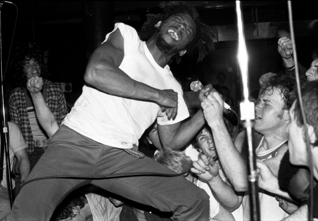 Black and white photo of punk musician performing surrounded by a crowd.
