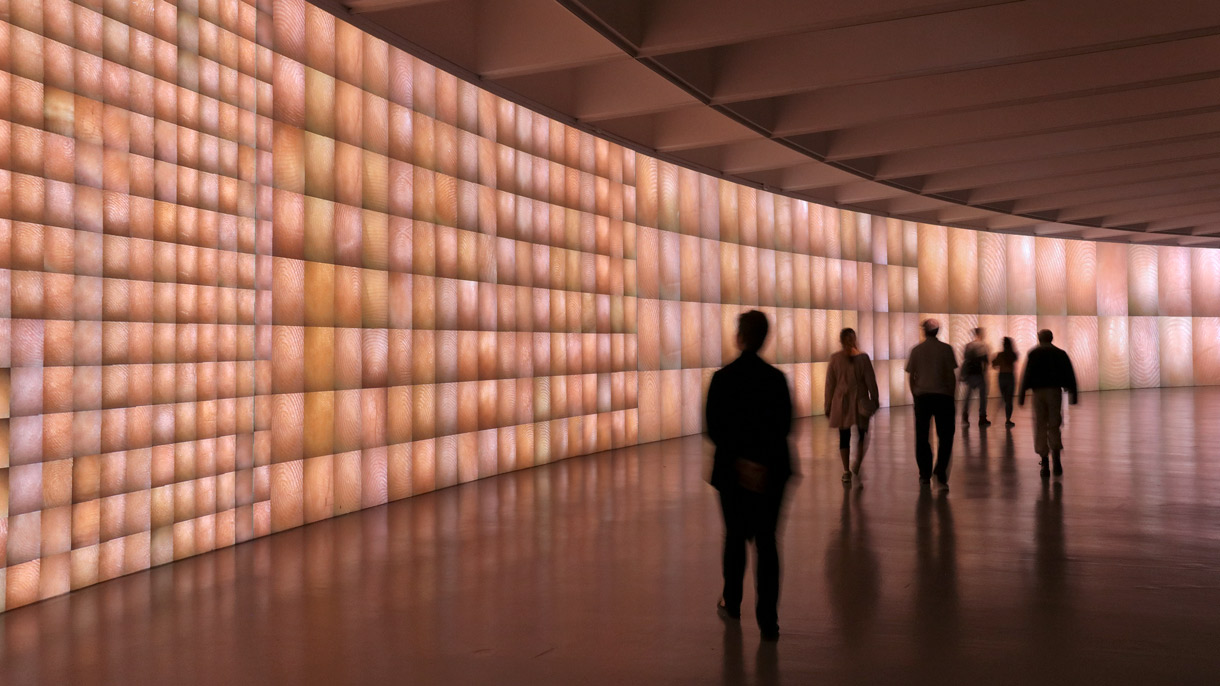 View of Raphael Lozano Hemmer's Pulse Index. Visitors walk along a gallery wall lit up with hundreds of finger prints.