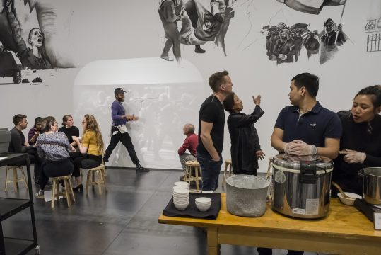 Installation view of Rirkrit Tiravanija: (who's afraid of red, yellow, and green). Visitors experiencing the culinary component, sharing curry.