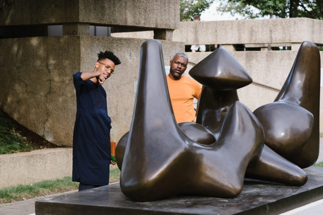 Two visitors examine a sculpture.