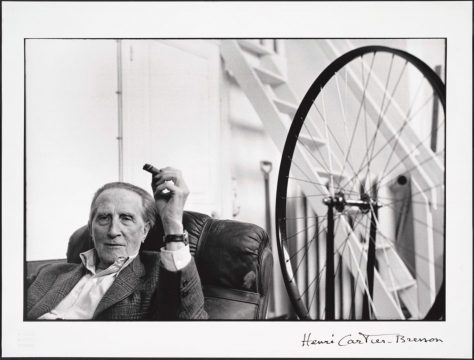 The artist sits in a leather chair wearing a suit jacket and holding a cigar. Next to him is a large bicycle wheel attached to a stool.