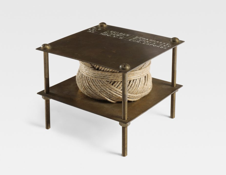 A ball of twine rests between two brass plates held together by screws.
