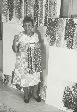 A black and white photo of the artist in her studio. She wears a patchwork style dress and stands holding one of her paintings.