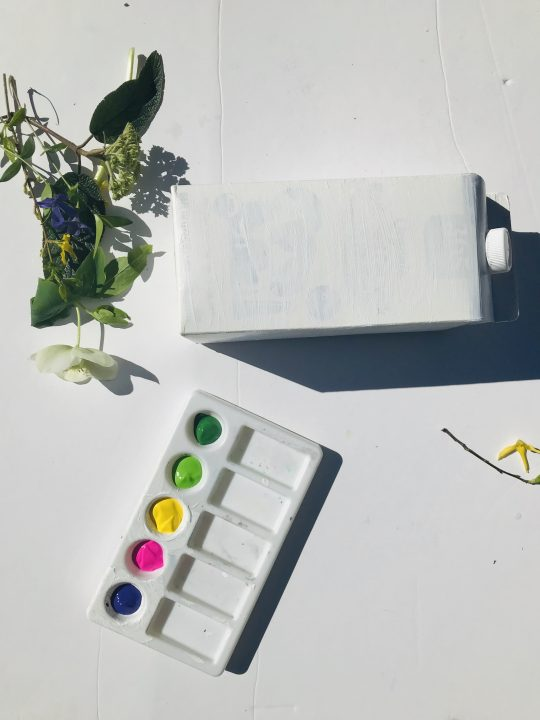Craft materials. Empty milk carton, paint, a bird perch, and glue