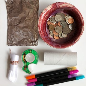 Dish with coins, toilet paper roll, markers, aluminum foil, tape, and fabric.
