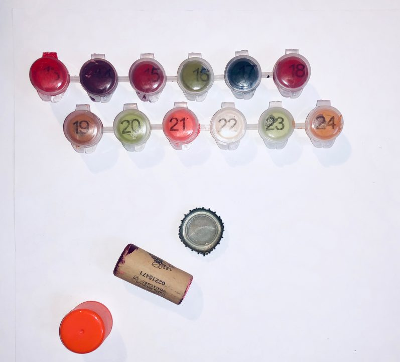 Various paints, cork, bottle cap, and film canister sitting on a white surface.