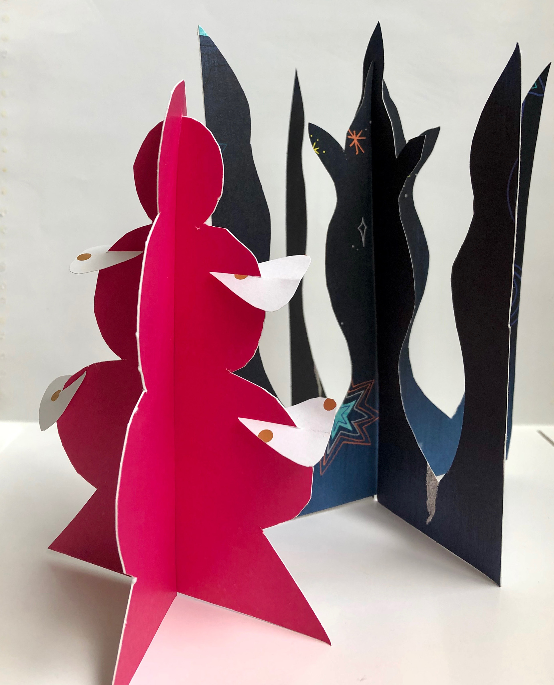 Two paper sculptures. Left sculpture is red and shapes like a tree. The one behind it to it's right is blue and looks like a trident spearhead.