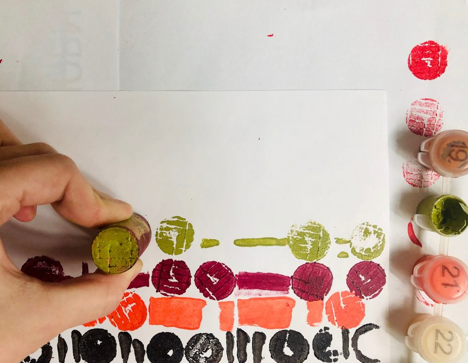 Hand stamping green paint on a piece of paper with a cork.