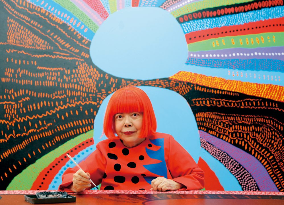 Portrait of Yayoi Kusama infront of a colorful painting.