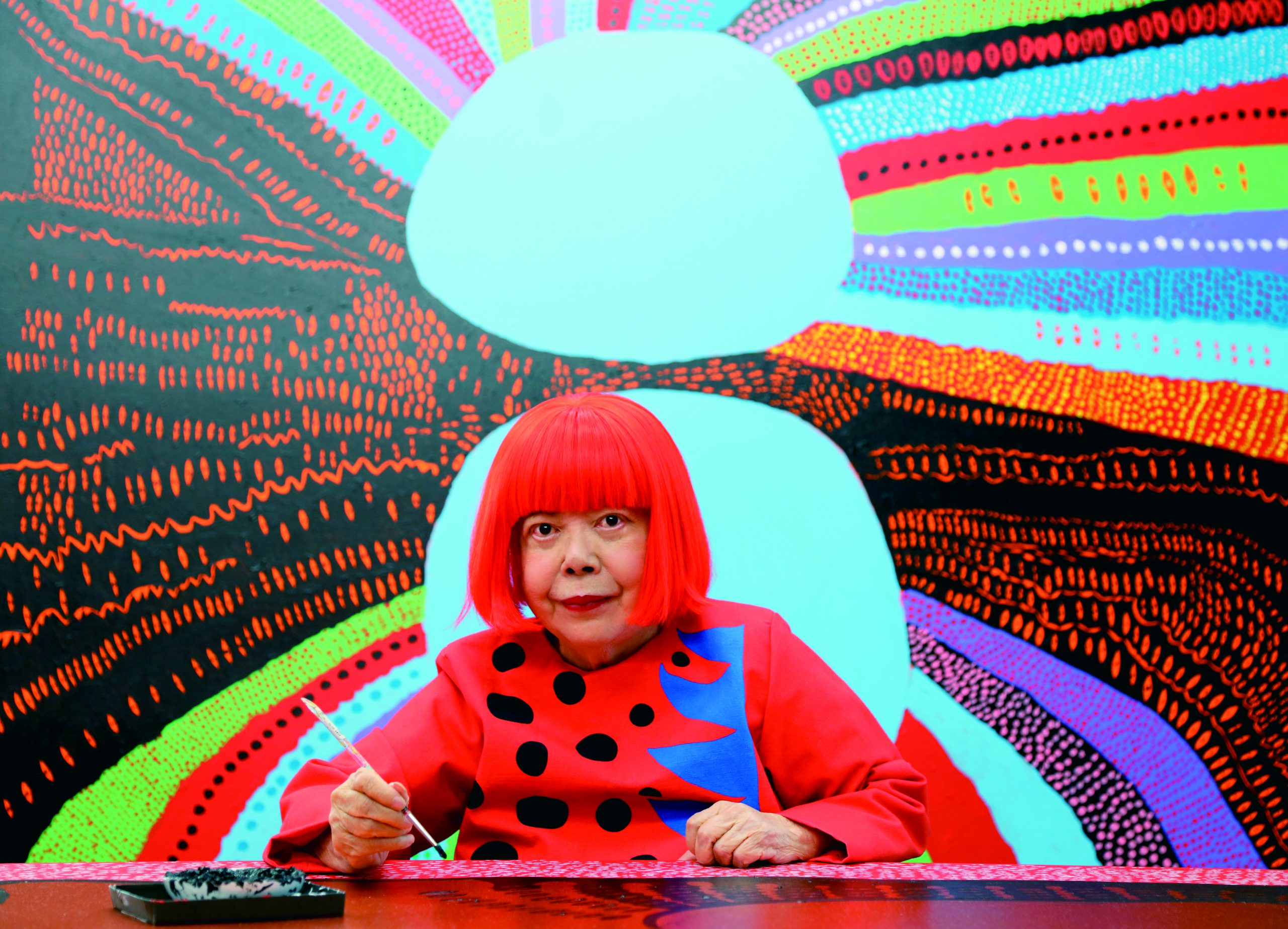 Portrait of Yayoi Kusama sitting in front of a colorful painting.