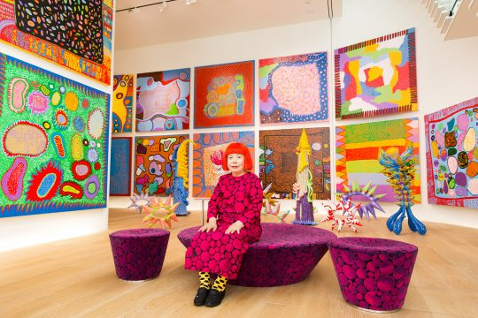 The artist wears a pink and black polka dotted dress. She is sitting on a bench that matches the pattern of her dress. There are large square paintings on the walls around her. The paintings are full of brightly colored shapes.