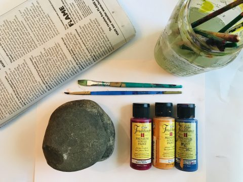 Folded newspaper, two paint brushes, a clean rock, three small bottles of paint, and a glass jar with paint brushes in dirty water