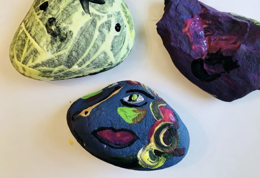 Three rocks, one painted yellow with black lines, one purple with pink lines, one blue with multicolored, misaligned facial features
