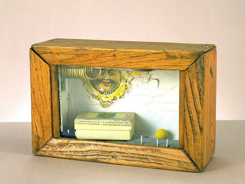 Glass-paned wooden box containing a metal coil, postage stamp of a boat, small paper box, yellow ball, white nails, blue sand, and a smiling sun in the background