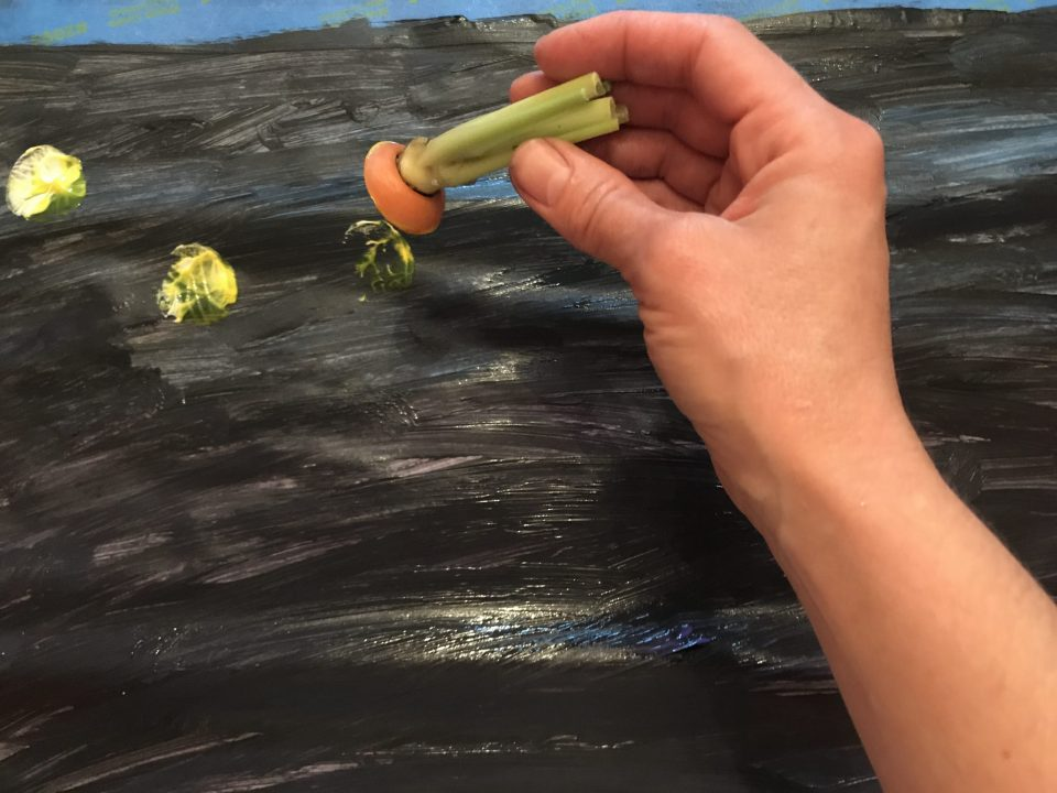 Hand using a sliced carrot to paint yellow dots on a black background