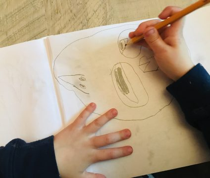 Pencil sketch of a face with two different sized eyes aligned vertically in the center, pointed nose on the left, mouth on the right. A child's hand is drawing the eye to the far right.