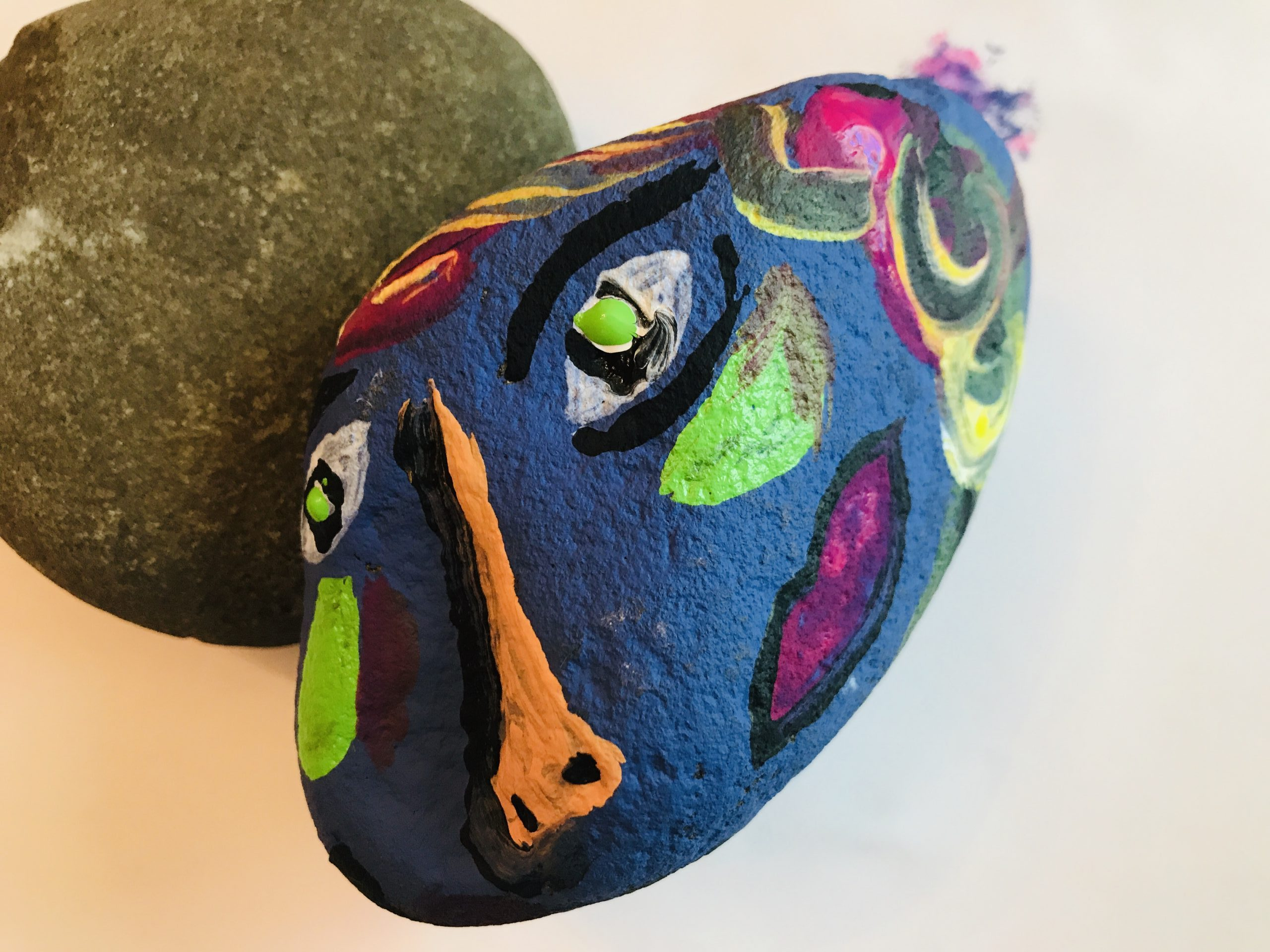 Face painted on a rock, with another non paint rock behind
