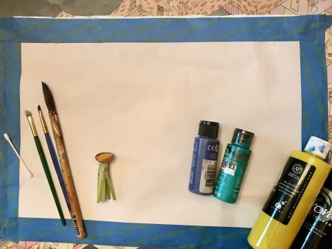 Paintbrushes, a cotton swab, a sliced carrot, and bottles of paint lie on a large piece of paper outlined with painter's tape