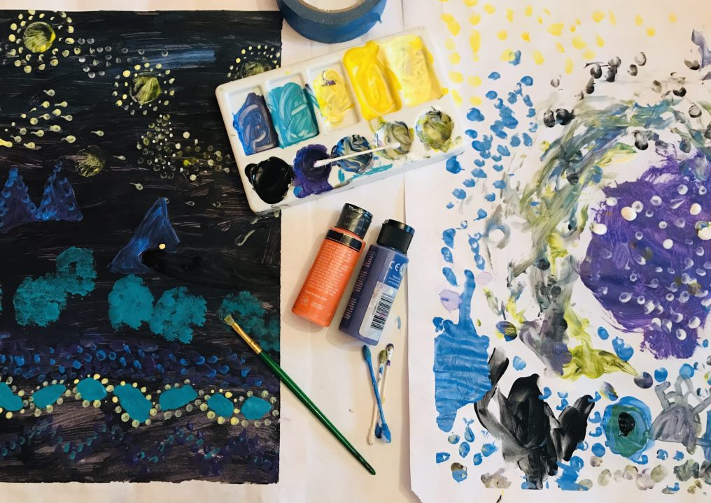 Palette filled with paint and jar filled with dirty water rest on a piece of paper, hand uses a cotton swab to apply paint to the paper