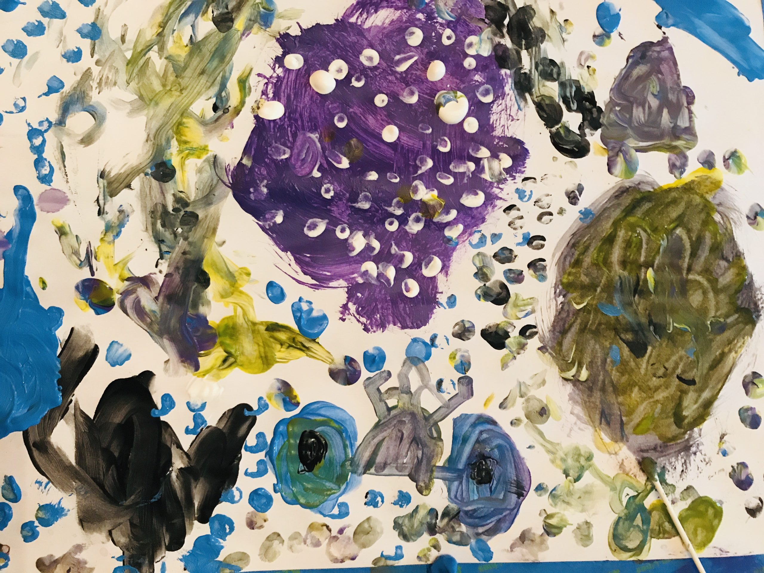 Palette with paint, a brush, cotton swabs, and two paint bottles sit between two finished abstract paintings on paper