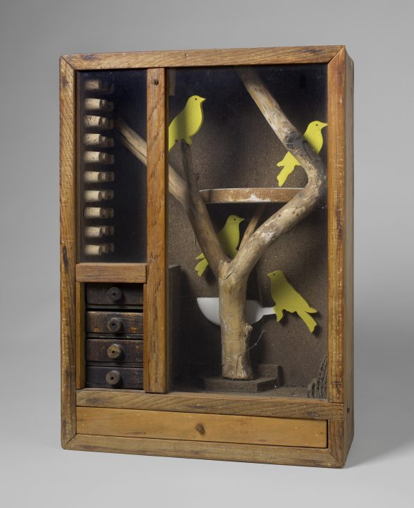 Glass-paned wooden box containing four yellow cardboard birds on a wooden branch, left inside wall of box is lined with corks above four miniature drawers