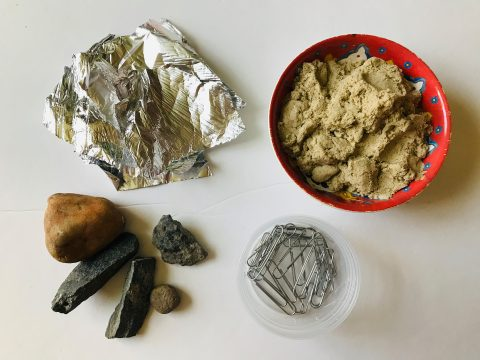 Foil, rocks, sand, and paperclips are displayed
