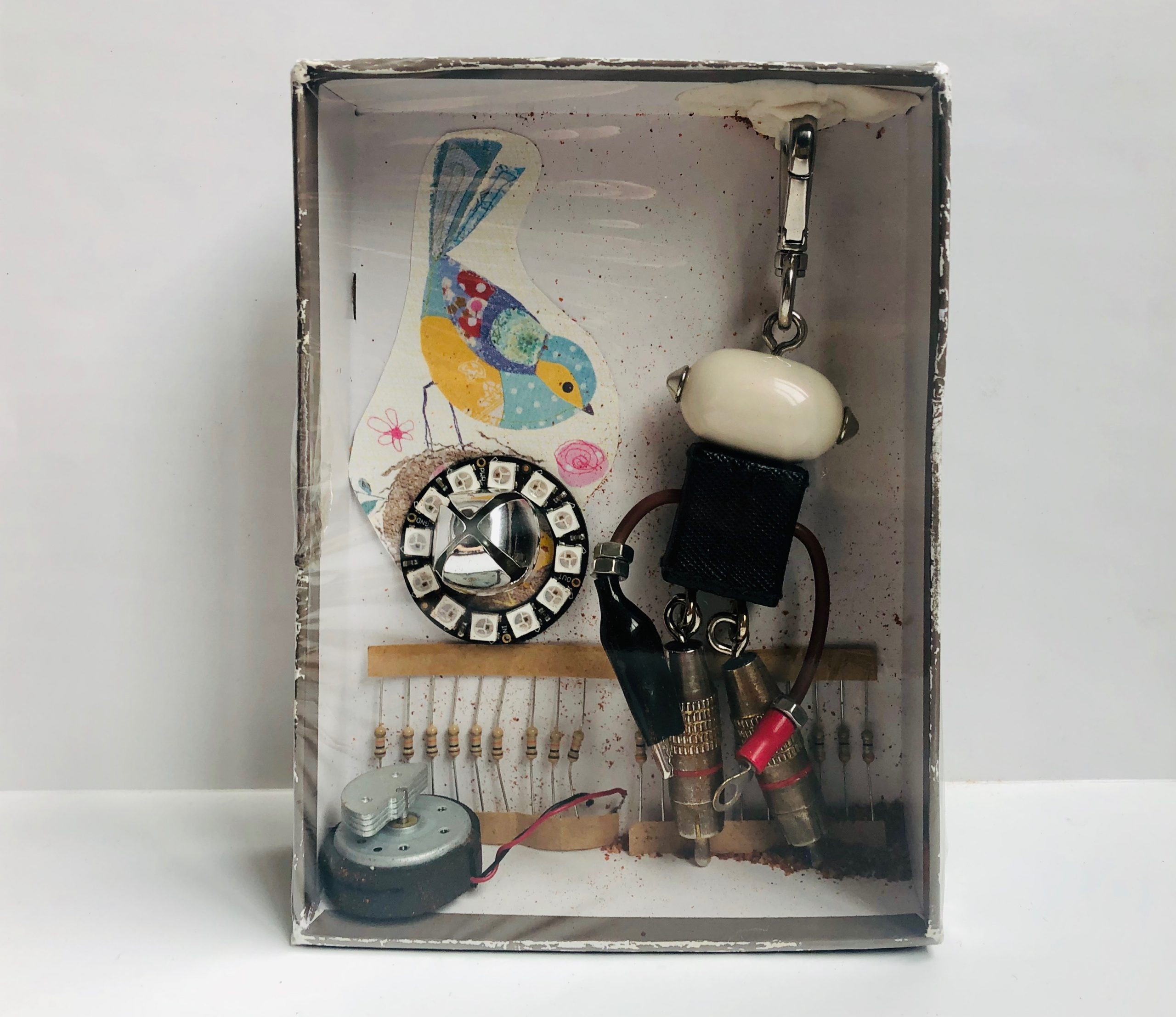 Final product of a small cardboard box covered with plastic wrap containing keychain, paper cutout of bird, jingle bell, resistors, and other found objects