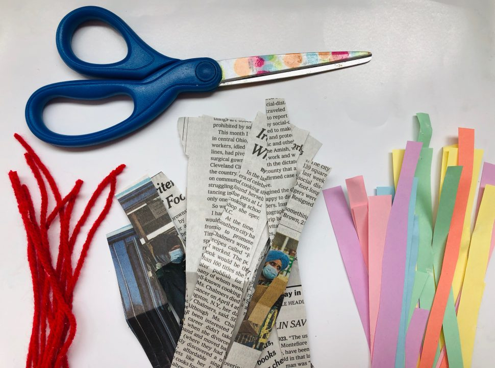 Pair of scissors lying above red yarn, newspaper, and multicolored paper all cut into strips