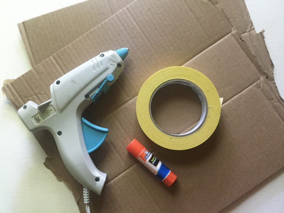 Hot glue gun, roll of masking tape, and glue stick lying on two pieces of square cardboard