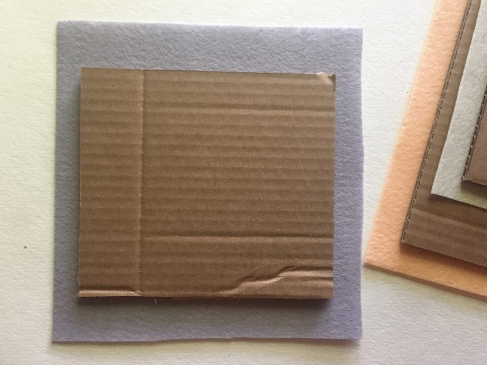 Square piece of cardboard glued on top of a square piece of gray felt