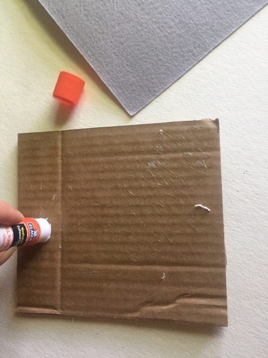 Hand applying glue to piece of square cardboard
