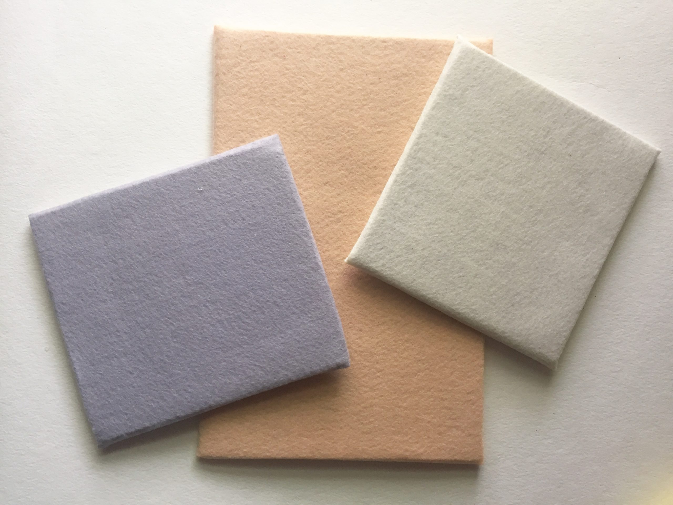 Three finished felt boards are displayed