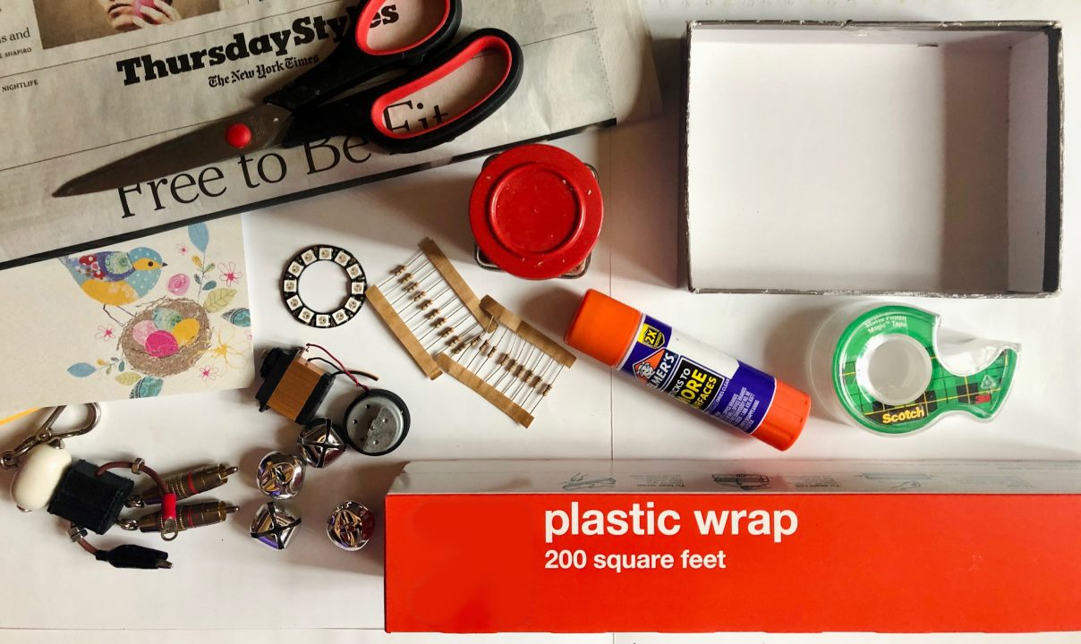 Pair of scissors on a newspaper, jar lid, glue stick, roll of tape, plastic wrap, four jingle bells, keychain, resistors, and more found objects
