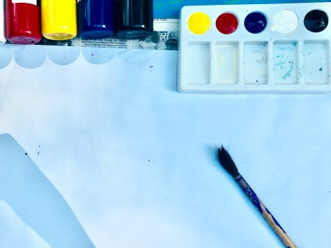 Overhead view of blank paper with paintbrush lying on it. Bottles of paint and a palette are at the top of the frame.