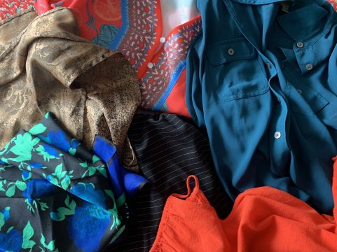Close-up of a pile of clothing including a red patterned blouse, tan scarf, black scarf with blue and green flowers, and plain red blouse.