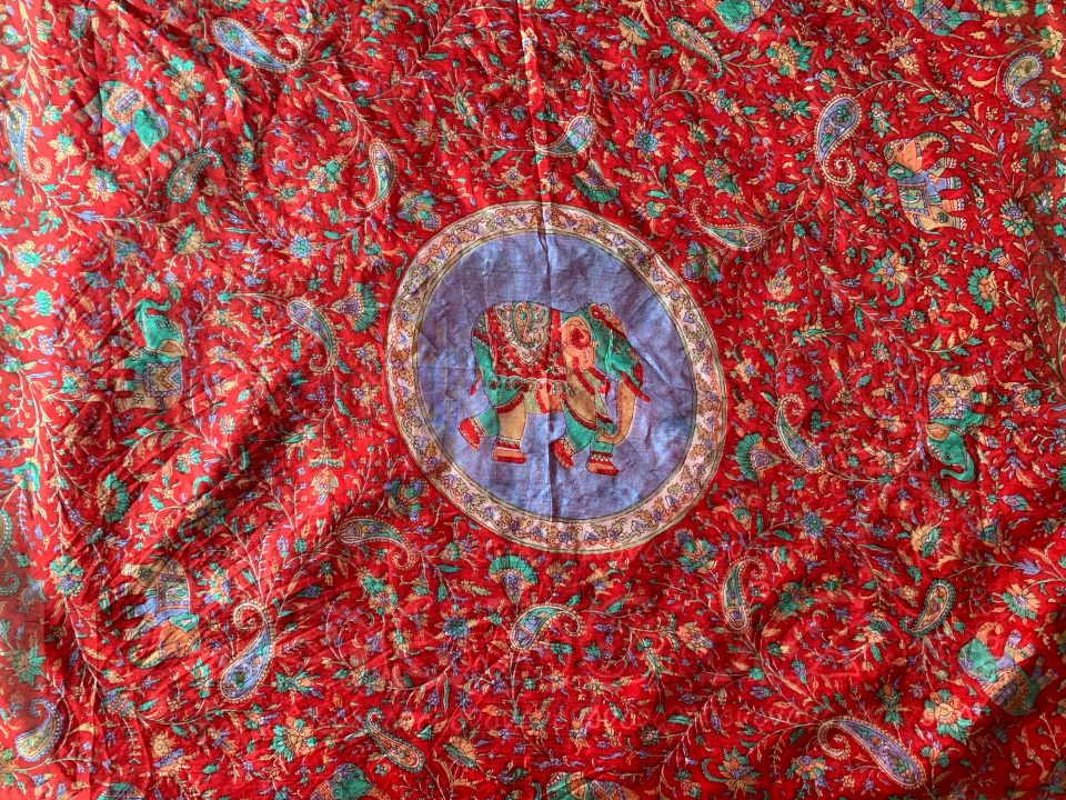 Large, red, paisley patterned scarf, laid flat.