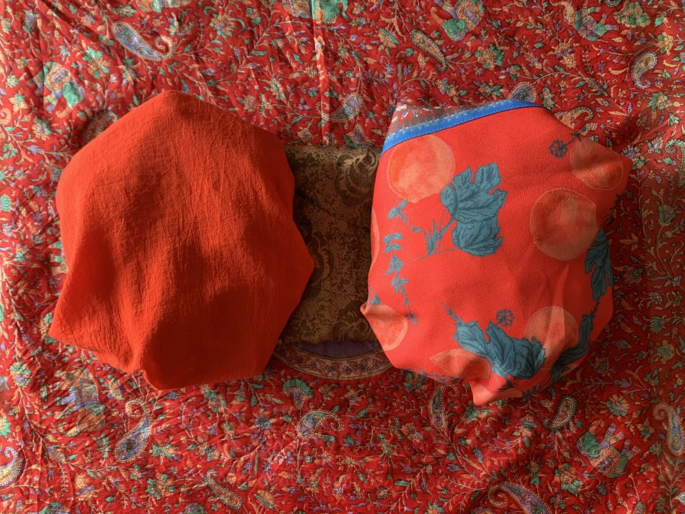 Two balled up shirts lie side by side on the red, paisley patterned scarf. One is plain red, the other is red with blue leaves.