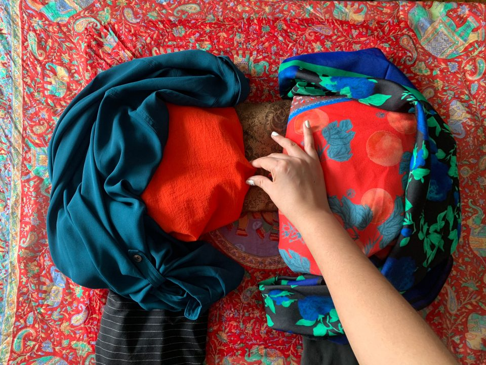 Blue shirt and black scarf are added to create the shape of two figures in profile facing each other, a hand reaches to pinch the fabric of one figure into a nose.