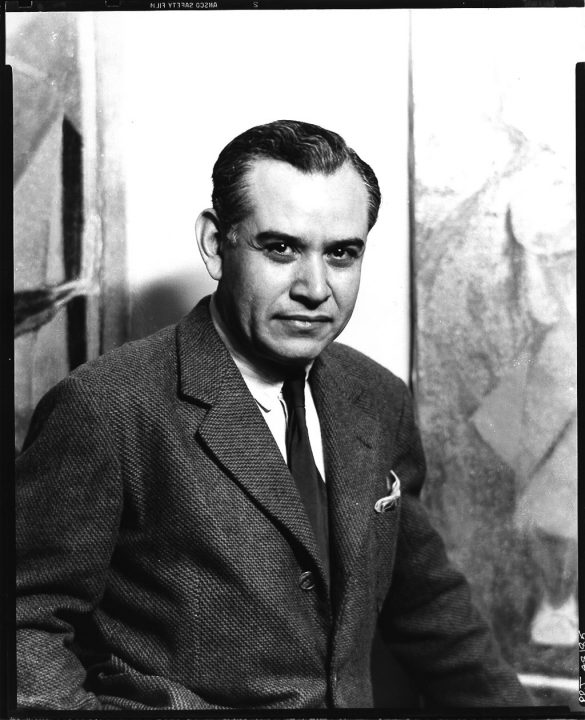 Black-and-white photograph of the artist sitting and smiling at the camera, his dark hair combed back, wearing a gray tweed jacket with white shirt and black tie.