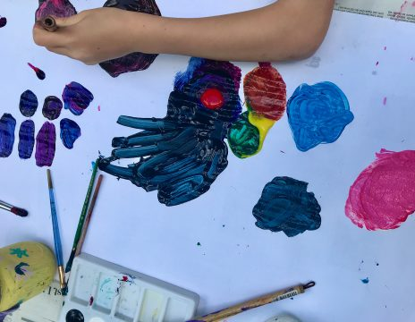 A hand applies paint to white paper. Paintbrushes and a palette are scattered across the bottom of the frame.