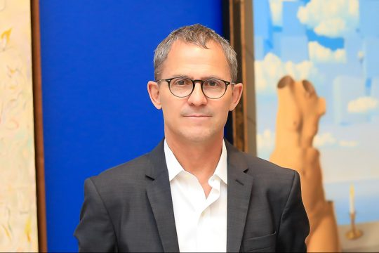 Chief curator Stephane Aquin standing in front of artwork in a gallery