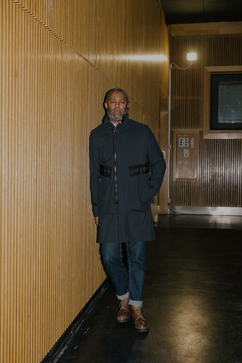 Artist Arthur Jafa standing against the wall in a wooden room