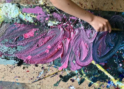 Cardboard surface covered with multicolored paint, a hand reaches to smear the paint with a brush.