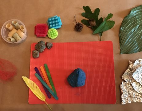 Rocks, popsicle sticks, a feather, and playdough lie on a red mat. Leaves, netting, tin foil, and dry pasta surround the mat.